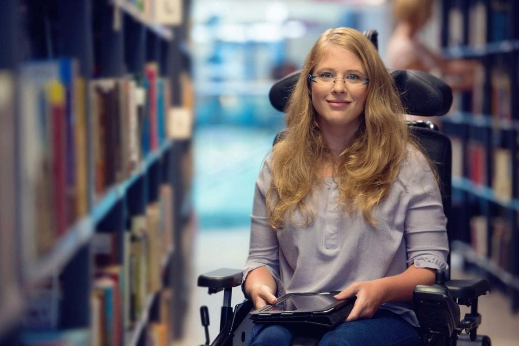 Disabled woman in wheelchair receiving assistive technology in Missouri - SADI