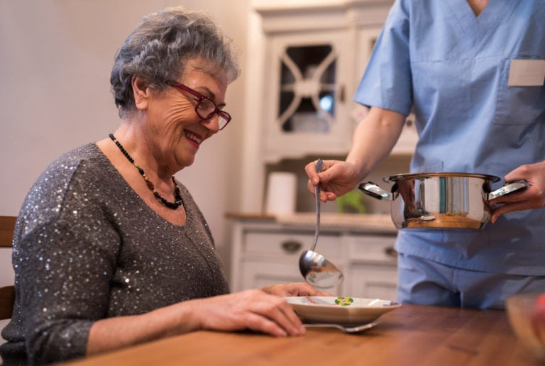 Nurse assisting senior disabled woman at home in Missouri