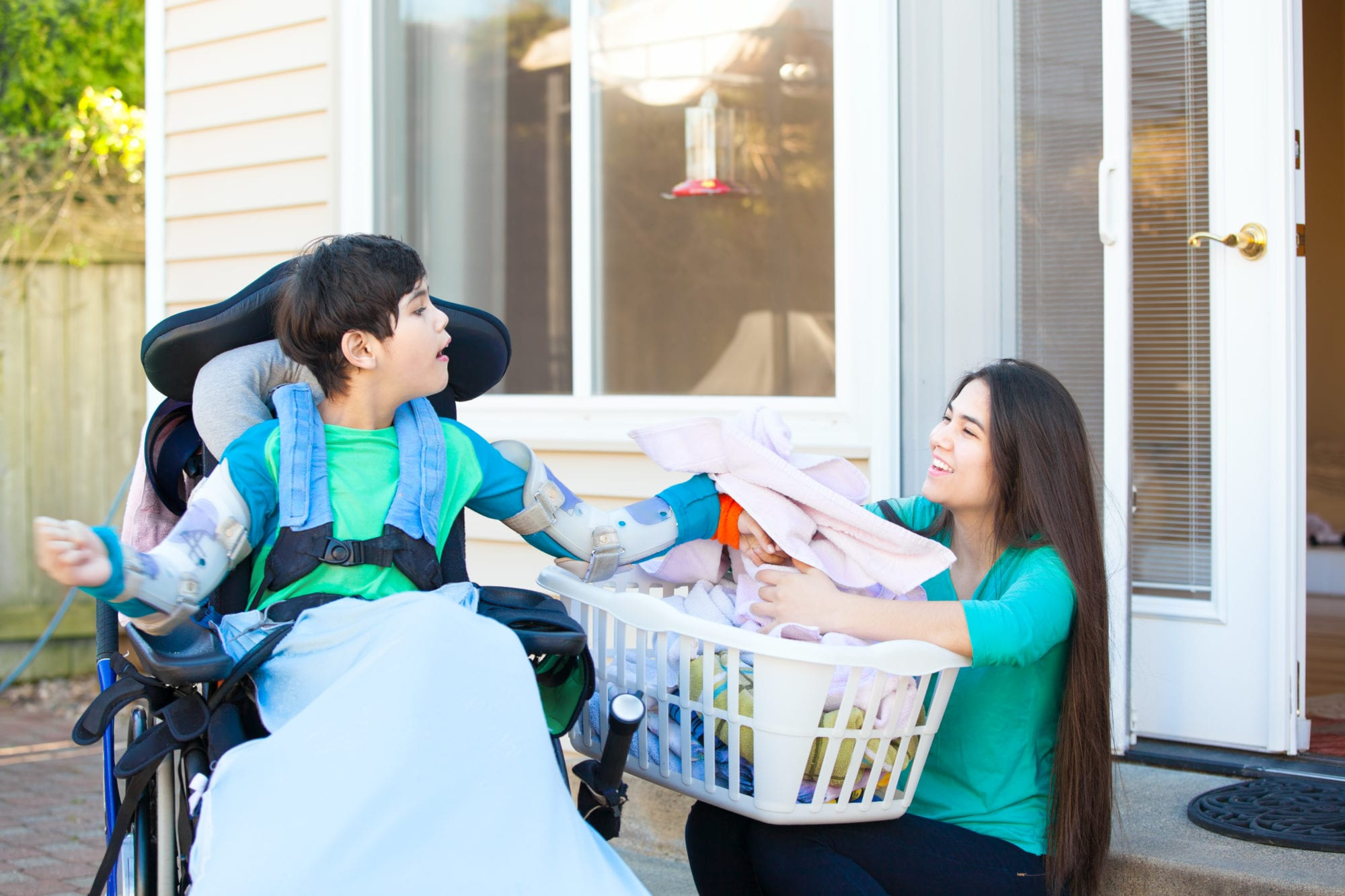 Disabled boy in wheelchair helping older sister fold laundry