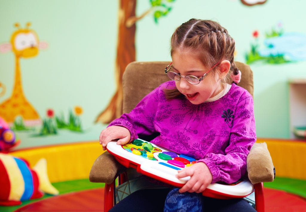 Young girl in a wheelchair playing with one of SADI's development toys in Missouri