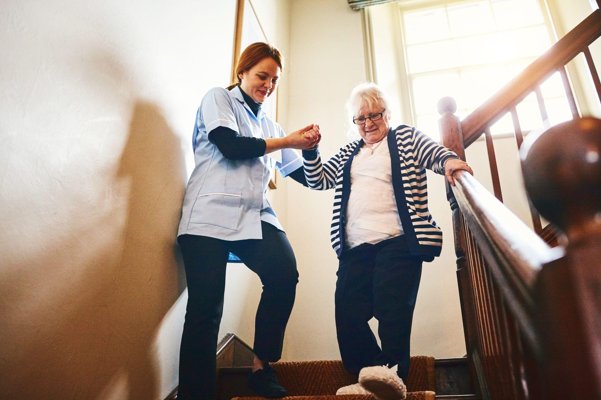 Caregiver helping senior woman walking down stairs