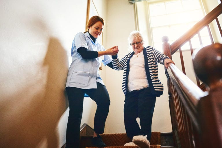 Caregiver helping senior woman walking down stairs