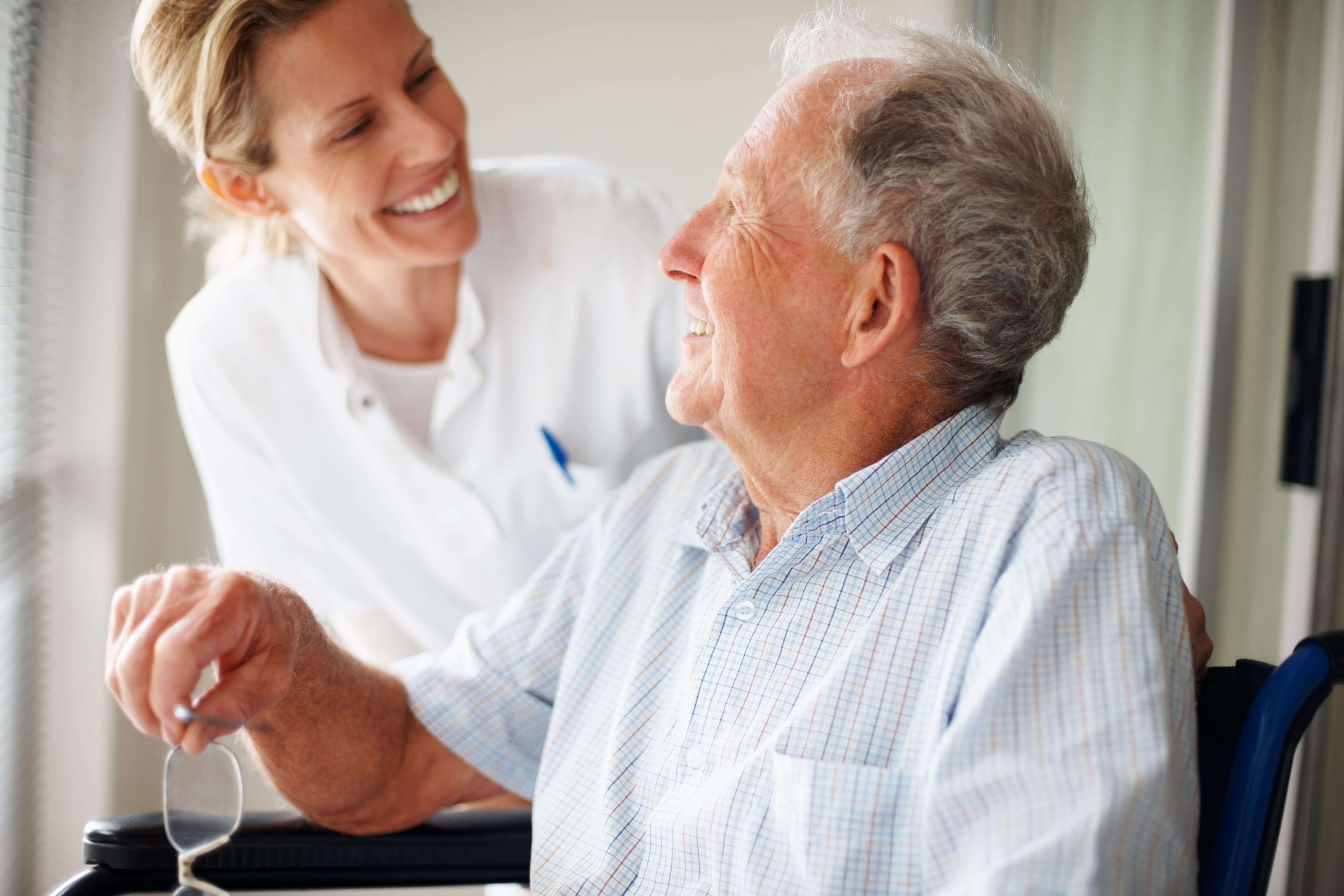 Elderly man speaking to a nurse