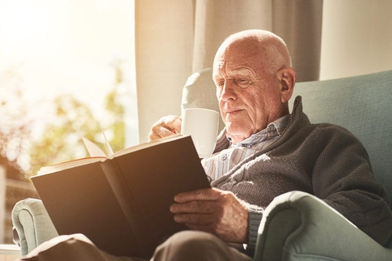 Elderly man reading a book at home