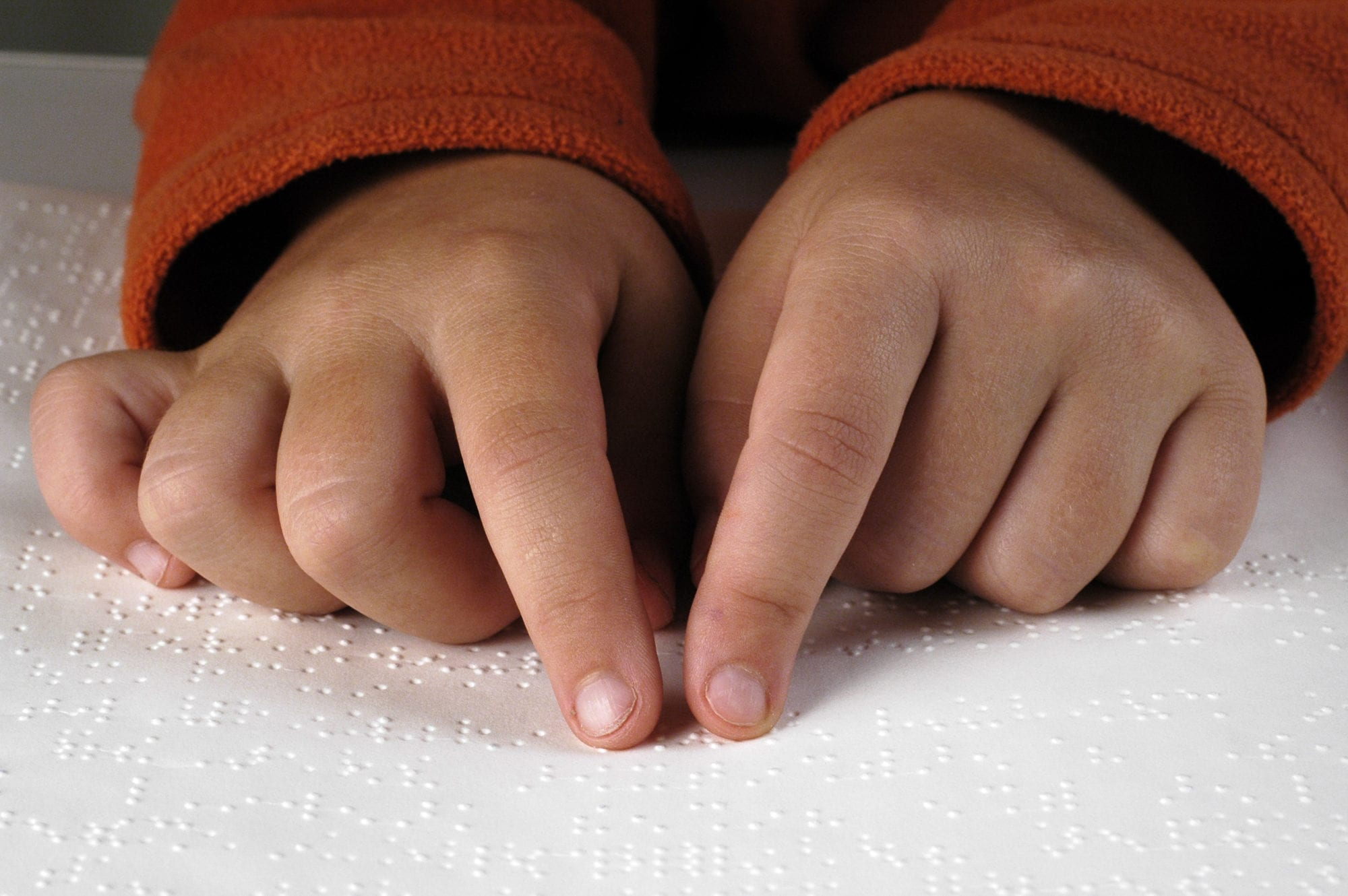 Young hands reading braille