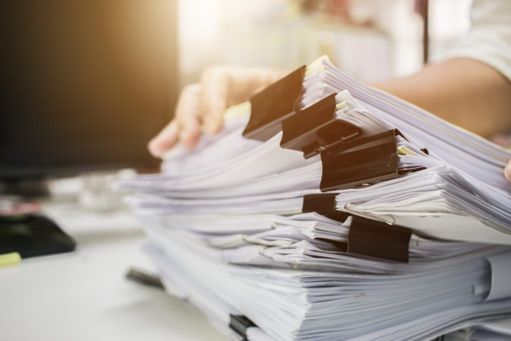 Stacks of paper files on work desk
